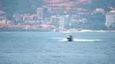 моторная лодка : Motorboat moving at sea against Mediterranean resort scenery