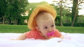 младенчество : Cute baby with pink pacifier laying on the towel on the grass