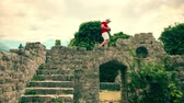amateur : Young man in red tshirt photographing ancient ruined buidings