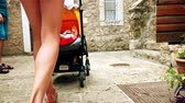 pram : Mom and her child traveling along narrow old town street with a stroller