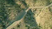 viraj : Aerial view of a red car moving along windy road in mountains