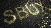 custo : Starbucks SBUX stock ticker made of gold numbers, conceptual editorial animation