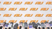 au : News conference of AU, press wall with logo as a background and mics, editorial animation