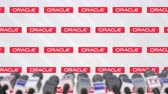mike : Media event of ORACLE, press wall with logo and microphones, editorial animation