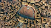 sloping : Aerial top down view of Siena cityscape involving famous Piazza del Campo or Campo Square. Tuscany, Italy