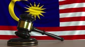 licit : Judges gavel and block against the flag of Malaysia. Malaysian court conceptual animation