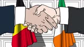 рукопожатие : Businessmen or politicians shake hands against flags of Belgium and Ireland. Official meeting or cooperation related cartoon animation Стоковые видеозаписи