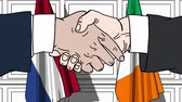 рукопожатие : Businessmen or politicians shake hands against flags of Netherlands and Ireland. Official meeting or cooperation related cartoon animation Стоковые видеозаписи