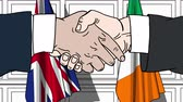 рукопожатие : Businessmen or politicians shake hands against flags of Great Britain and Ireland. Official meeting or cooperation related cartoon animation