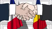 rumunia : Businessmen or politicians shake hands against flags of France and Romania. Official meeting or cooperation related cartoon animation