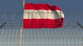 restringido : Defocused waving flag of Austria behind barbed wire fence. Loopable 3D animation Stock Footage