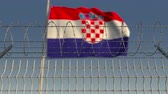restringido : Blurred waving flag of Croatia behind barbed wire fence. Loopable 3D animation Stock Footage
