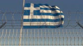 フロンティア : Barbed wire against waving flag of Greece. Loopable 3D animation