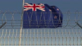 fronteira : Defocused waving flag of New Zealand behind barbed wire fence. Loopable 3D animation