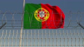 portugalia : Defocused waving flag of Portugal behind barbed wire fence. Loopable 3D animation