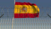fronteira : Barbed wire against waving flag of Spain. Loopable 3D animation