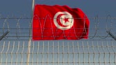 フロンティア : Barbed wire against waving flag of Tunisia. Loopable 3D animation