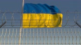 ucrânia : Blurred waving flag of Ukraine behind barbed wire fence. Loopable 3D animation Vídeos
