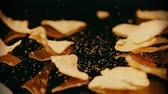 aperitivos : Tortilla chips fall and crumble on black background, slow motion shot