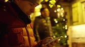 oddech : Handsome young man in red jacket uses his smartphone in the evening against Christmas illumination. Shot on Red camera Wideo
