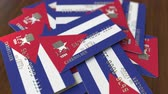 küba : Pile of credit cards with flag of Cuba. Cuban banking system conceptual 3D animation