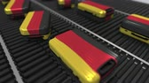 roller conveyor : Suitcases featuring flag of Germany move on the conveyor in an airport. German tourism related loopable animation