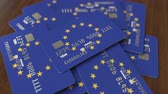 economics : Pile of credit cards with flag of the European Union. EU banking system conceptual 3D animation