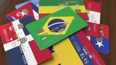 cardholder : Many credit cards with different flags, emphasized bank card with flag of Brazil