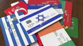 credito : Many credit cards with different flags, emphasized bank card with flag of Israel Archivo de Video