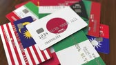 cardholder : Many credit cards with different flags, emphasized bank card with flag of Japan