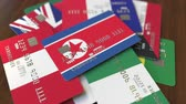 cardholder : Many credit cards with different flags, emphasized bank card with flag of North Korea