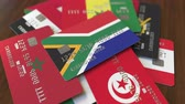 cardholder : Many credit cards with different flags, emphasized bank card with flag of South Africa Stock Footage