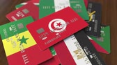 チュニジア : Many credit cards with different flags, emphasized bank card with flag of Tunisia 動画素材