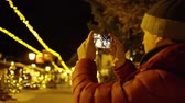 夜遊び : Unknown young man in red jacket makes photos with smartphone in the evening on Christmas illumination background. Shot on Red camera 動画素材
