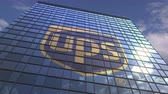 средства массовой информации : UPS logo against modern building reflecting sky and clouds, editorial animation