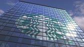 yansıtıcı : STARBUCKS logo against modern building reflecting sky and clouds, editorial animation Stok Video