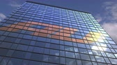 au : AU logo on modern building reflecting sky and clouds, editorial animation