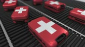 roller conveyor : Many travel suitcases featuring flag of Switzerland on roller conveyer. Swiss tourism conceptual animation Stock Footage