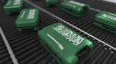 roller conveyor : Many travel suitcases featuring flag of Saudi Arabia on roller conveyer. Saudi tourism conceptual animation