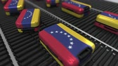 manuseio : Many travel suitcases featuring flag of Venezuela on roller conveyer. Venezuelan tourism conceptual animation Stock Footage
