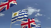 negocjacje : Flags of Uruguay and the United Kingdom against blue sky, loopable 3D animation Wideo