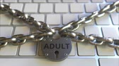 cadarço : Padlock with ADULT text on the computer keyboard. Blocking or restriction related 3D animation Stock Footage