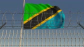 şaft : National flag of Tanzania behind barbed wire fence. Conceptual loopable 3D animation