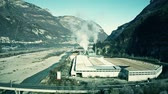stack : Aerial shot of air polluting plant in the river valley in northern Italy