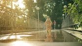 véd : Little baby girl in orange waterproof raincoat and rubber rain boots walks on puddles to her mother, slow motion shot