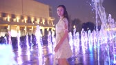 yalınayak : Beautiful young woman dances in the illuminated fountain in the evening, slow motion