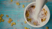 kukoricapehely : Adding milk to corn flakes on blue wooden table, top down super slow motion shot Stock mozgókép