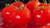 加える : Slow motion close-up shot of red cherry tomato falling down in red juice or sauce