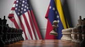 oposicion : Flags of United States and Venezuela behind chess board. The first pawn moves in the beginning of the game. Political rivalry conceptual 3D animation Archivo de Video