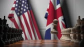 oposicion : Flags of United States and United Kingdom behind chess board. The first pawn moves in the beginning of the game. Political rivalry conceptual 3D animation